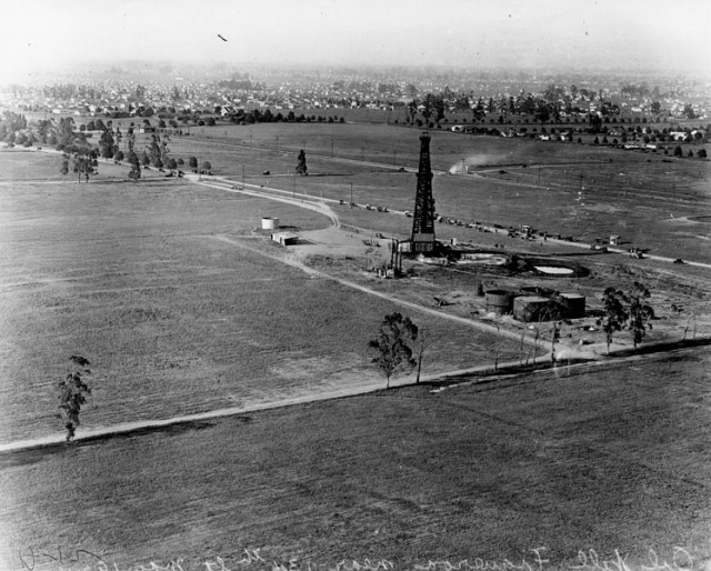 Figure 3:  For most of the twentieth century, oil derricks and small family farms lined much of the strip. Photo of Figueroa Street near 134th. Source: Los Angeles Public Library, Security Pacific National Bank Collection  (http://jpg1.lapl.org/pics36/00037755.jpg)